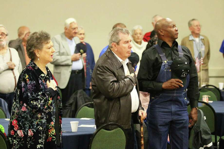 Veterans and their family members with their hand over their heart during the pledge of allegiance and as they observe the presentation of colors. Photo: David Taylor / HCN