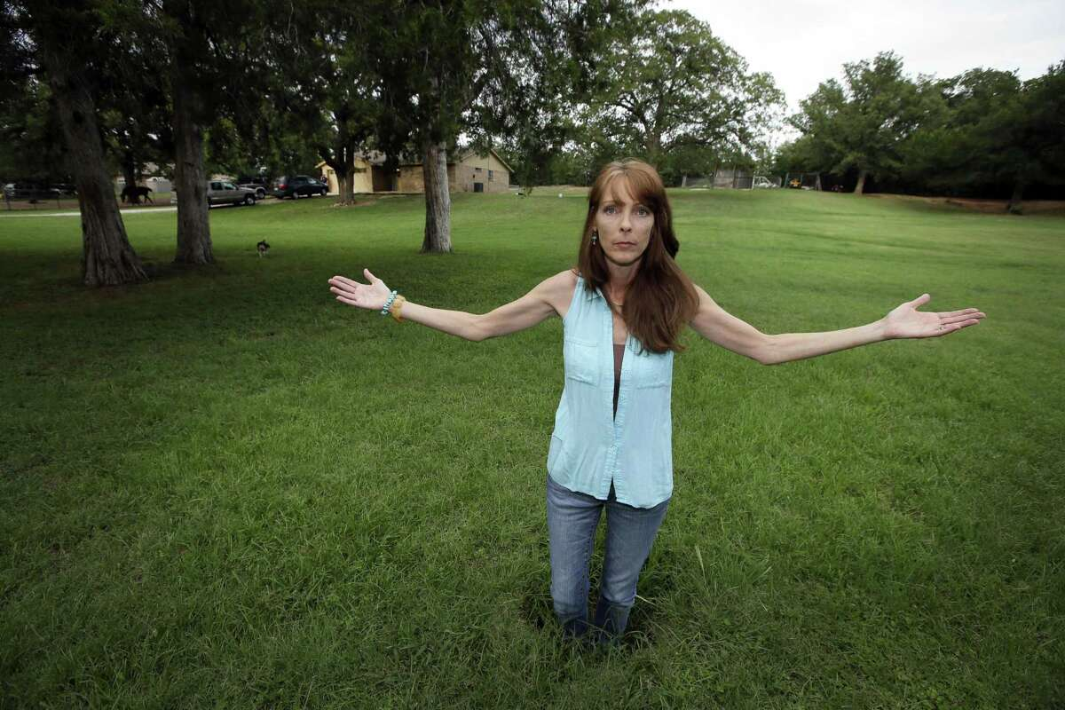 Barbara Brown poses for a photo standing knee deep in a sinkhole in front of her home in Reno, Texas, in 2014. She said oil and gas-related water disposal in the area caused earthquakes that damaged her home, causing sinkholes and foundation issues that led her and her family to abandon what she called her