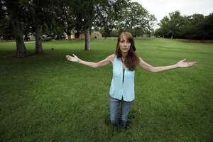 """Barbara Brown poses for a photo standing knee deep in a sinkhole in front of her home in Reno, Texas, in 2014. She said oil and gas-related water disposal in the area caused earthquakes that damaged her home, causing sinkholes and foundation issues that led her and her family to abandon what she called her """"forever home,"""" which fell into foreclosure."""
