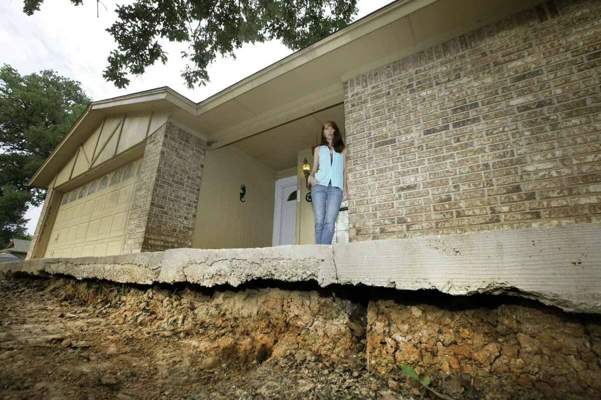 Barbara Brown poses for a photo by the front step of her home that now sits about one foot off the surface of her lawn, Reno, Texas, in 2014. She said oil and gas-related water disposal in the area caused earthquakes that damaged her home, causing sinkholes and foundation issues that led her and her family to abandon what she called her
