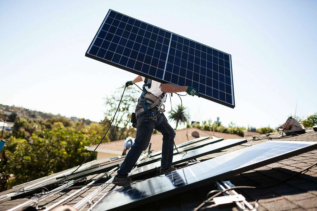 A Sunrun installer carries a solar panel into place at a customer's home in Carlsbad, Calif., Oct. 18, 2018. Tesla is relying on showrooms to sell electric cars, solar roofs and batteries. But a California rival has made inroads into the residential business. (Collin Chappelle/The New York Times)