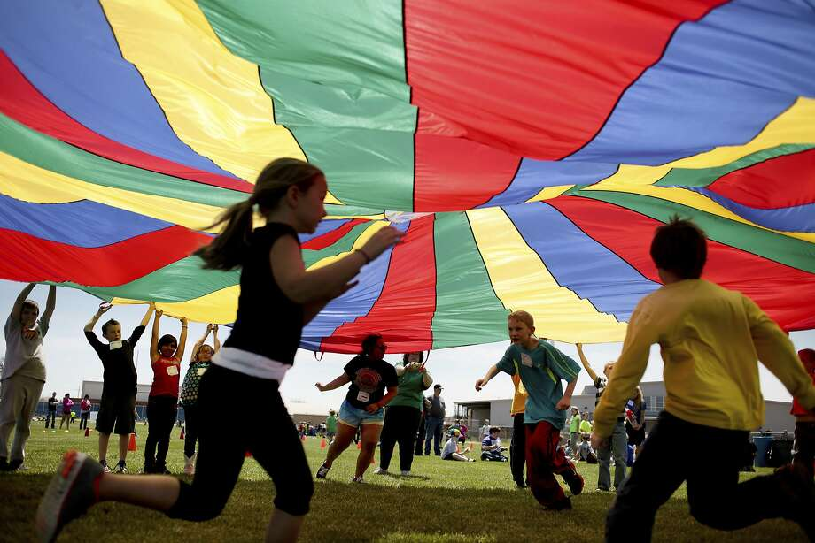 Elementary school students romp under a tarp at a Kansas Kids Fitness Day in Hutchinson, Kan., in 2013. New federal guidelines stress the benefits of physical activity as early as age 3. Photo: Aaron Marineau / Hutchinson (Kansas) News 2013