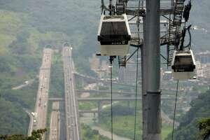 At an elevation of about 300 meters (984 feet) above a major highway, the new Maokong gondola travels over its four kilometer (2.5 mile) route during trial runs Thursday, June 28, 2007, in Taipei, Taiwan. (AP Photo/Wally Santana)
