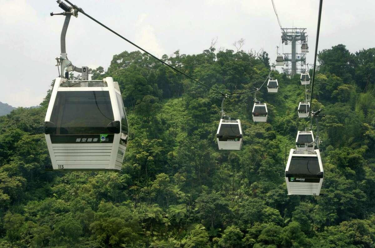The new Maokong gondola travels over its four kilometer (2.5 mile) route during trial runs Thursday, June 28, 2007, in Taipei, Taiwan. (AP Photo/Wally Santana)