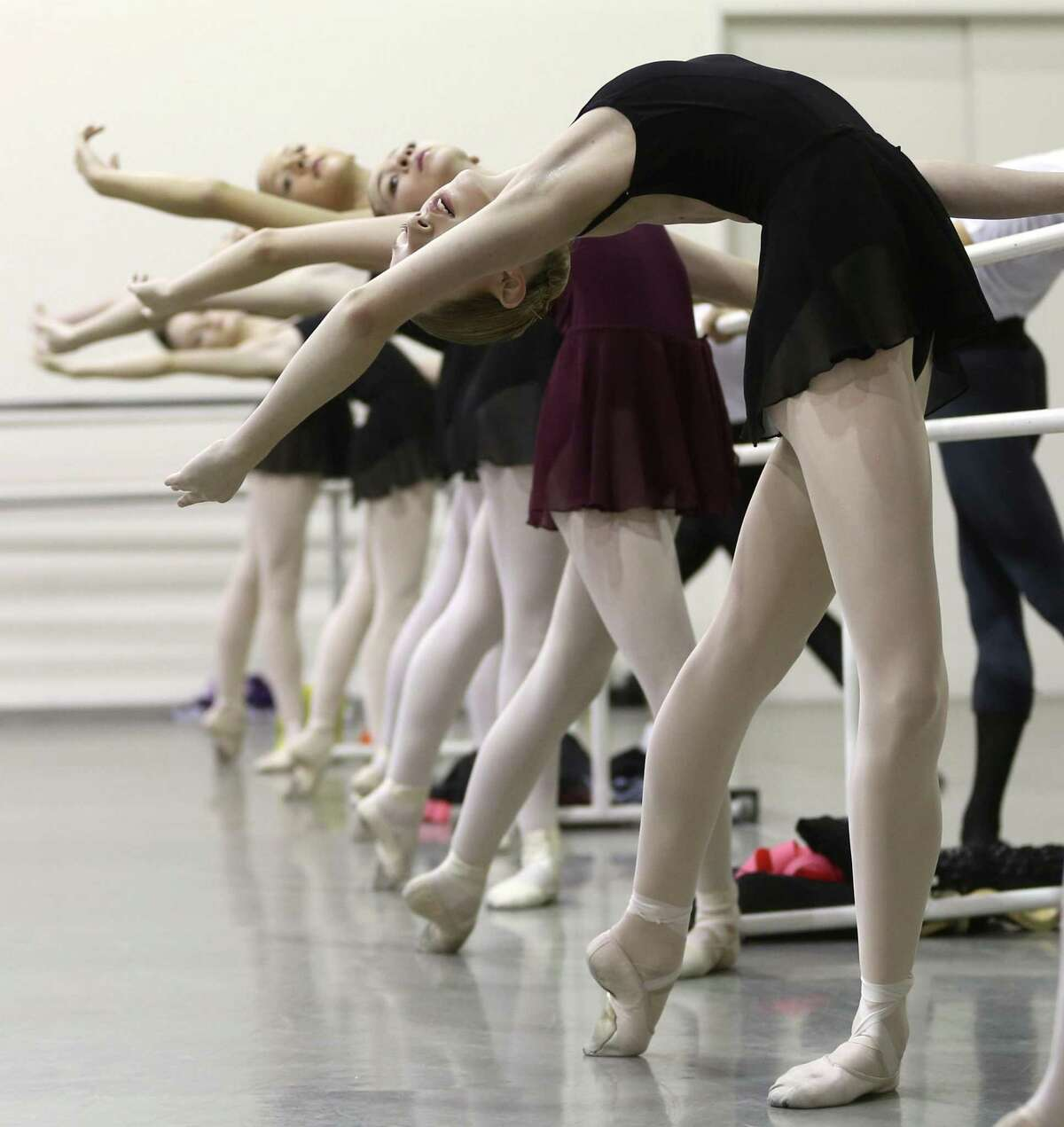 Dancer Lucy Hassmann, front, stretches with other Children's Ballet of San Antonio students before the start of rehearsal at Vanessa Bessler's studio.