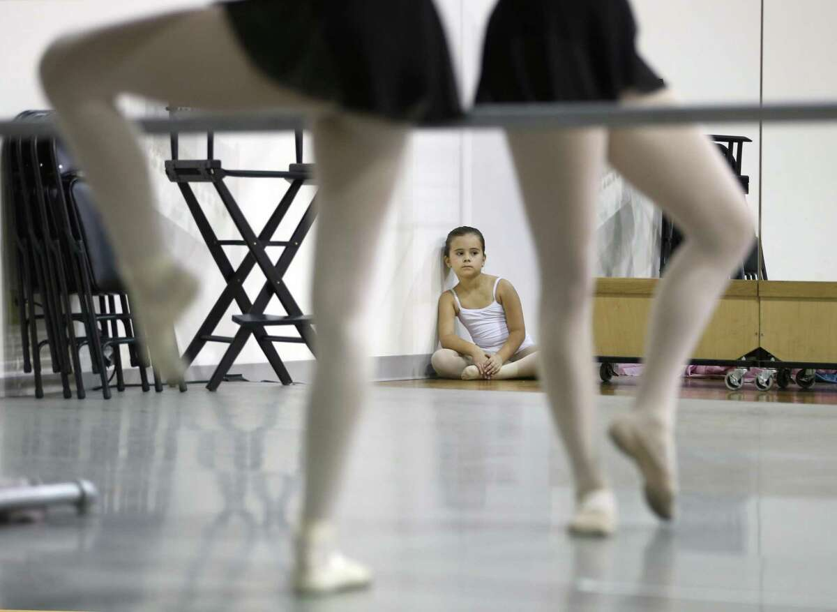 Talia Todd, 7, watches as dancers with the Children's Ballet of San Antonio stretch before the start of rehearsal.