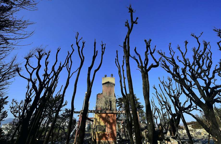 "The remains of a luxury home stand amid burnt out tree trunks in the beachside community of Point Dume in Malibu, California, on November 11, 2018, as the battle to control the Woolsey Fire continues. - Near Los Angeles, where the ""Woolsey Fire"" is threatening mansions and mobile homes alike in the coastal celebrity redoubt of Malibu, the death toll has been limited to two victims found in a vehicle on a private driveway.  Photo: FREDERIC J. BROWN, AFP/Getty Images"