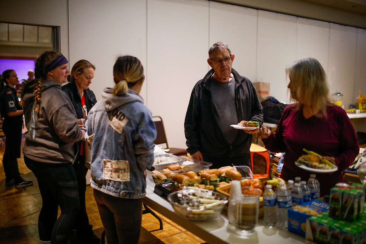 Camp Fire evacuee Norm Wright (center) gets a bite to eat for lunch at the Red Cross shelter in Chico, California, on Friday, Nov. 9, 2018.