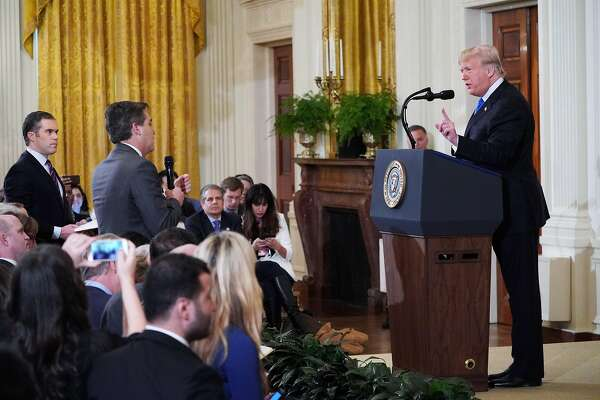 TOPSHOT - US President Donald Trump (R) gets into a heated exchange with CNN chief White House correspondent Jim Acosta (C) as NBC correspondent Peter Alexander (L) looks on during a post-election press conference in the East Room of the White House in Washington, DC on November 7, 2018. (Photo by MANDEL NGAN / AFP)MANDEL NGAN/AFP/Getty Images