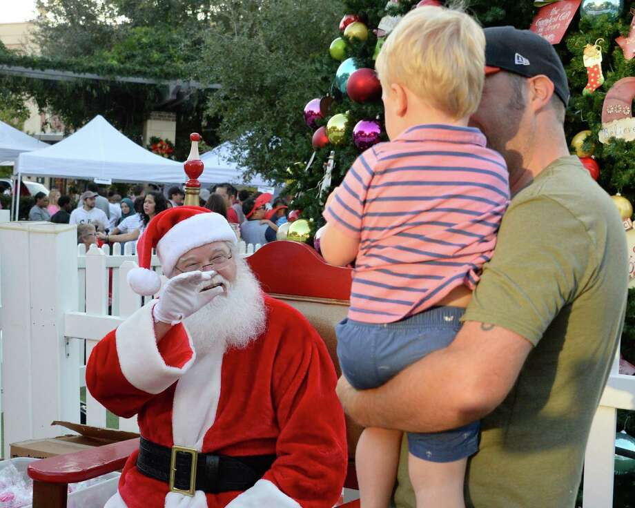 LaCenterra at Cinco Ranch will host its annual Tree Lighting Celebration from 6-9 p.m. Friday, Nov. 16, at 23501 Cinco Ranch Blvd., Katy. Above, Wayne Lacey and son, Dexter, visit with Santa Claus during the LaCenterra at Cinco Ranch 10th annual Tree Lighting Celebration. Photo: Craig Moseley, Staff / Chronicle / ©2017 Houston Chronicle