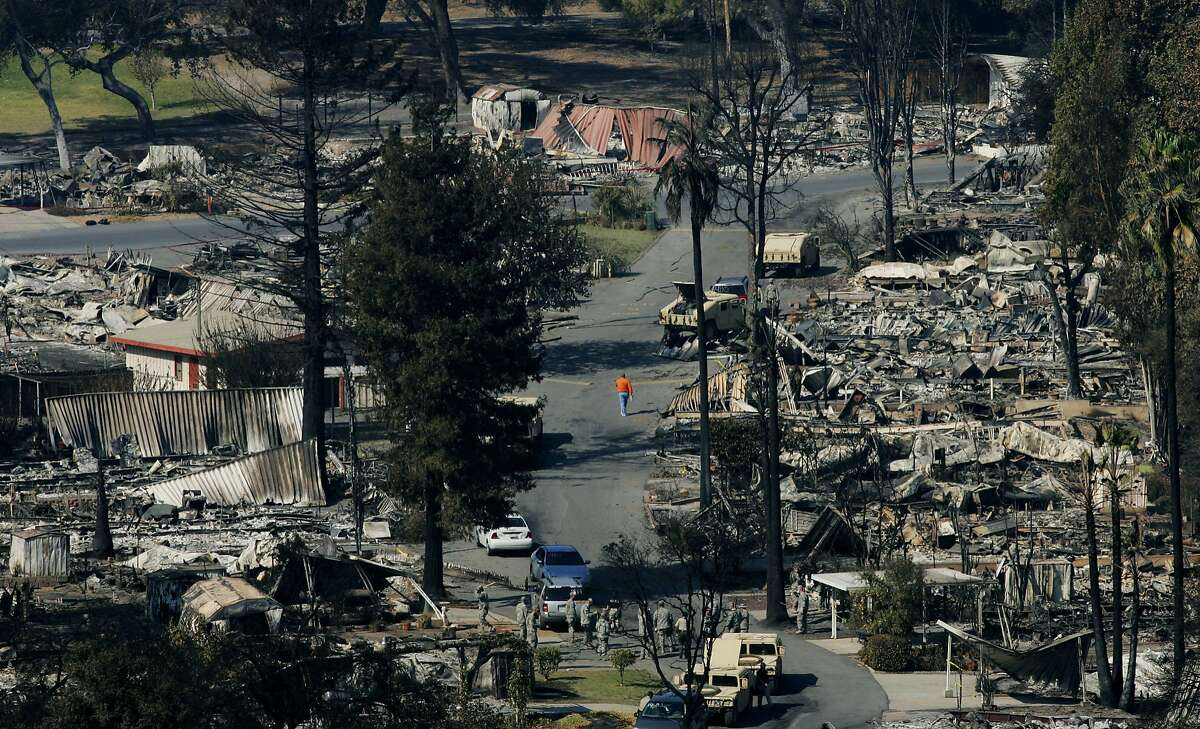 FALLBROOK, CA - OCTOBER 26: A person walks down a street littered with burned-out mobile homes October 26, 2007 in Fallbrook, California. The Witch Fire, which started outside of Ramona, CA, has burned hundreds of structures and forced thousands of evacuations as fires rage across Southern California. With improving weather conditions firefighters continued to make progress against the wildfires in California. The fires caused the largest mass evacuation in California's history, burning nearly 500,000 acres, leaving a heavy toll on the county's agricultural industry and impacting an estimated cost to the state of one billion dollars. (Photo by Sandy Huffaker/Getty Images)