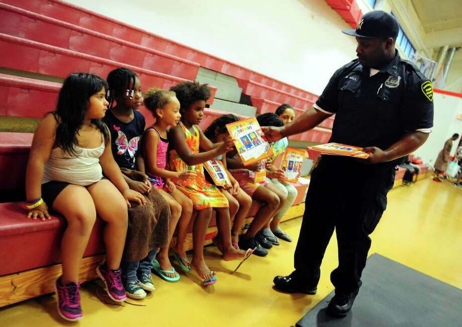 Security officer Harry Bell, who has created a Color a Positive Thought coloring book for kids, hands out ccopies of the book to some of the kids he mentors at the Trumbull Gardens Community Center in Bridgeport, Conn., on Thursday July 7, 2016. He has organized the first annual Empowering Kids Day planned for July 15 at Seaside Park. Photo: Christian Abraham / Hearst Connecticut Media / Connecticut Post