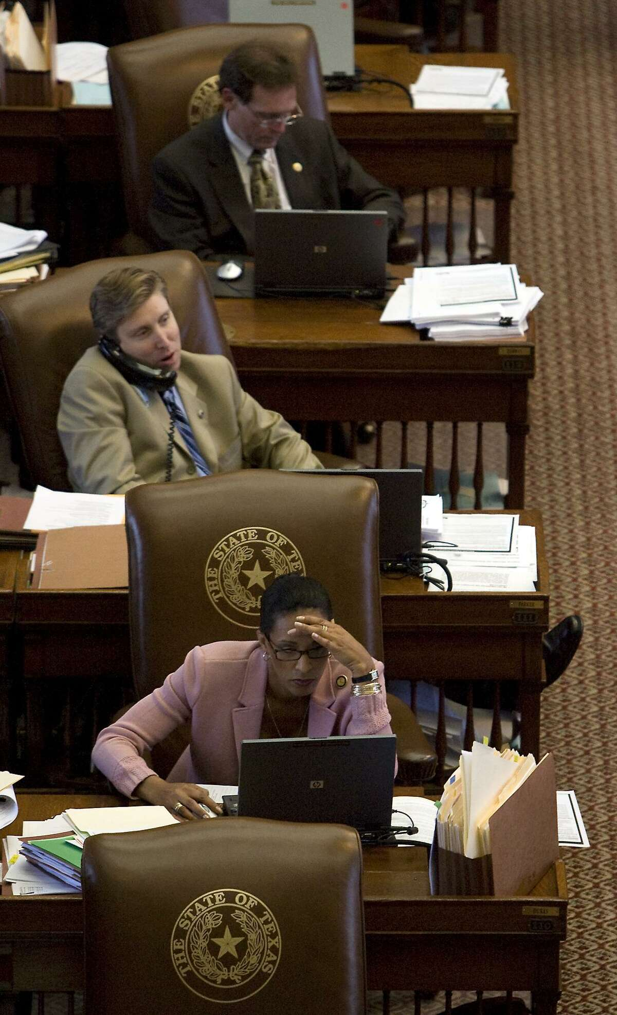State Representatives Dawna Dukes, Tan Parker (middle) and John Zerwas at work during the session Thursday, May 14, 2009. May 14, 2009. Photo by Larry Kolvoord. Both Parker and Zerwas have withdrawn their candidacies for House Speaker in the last few weeks.