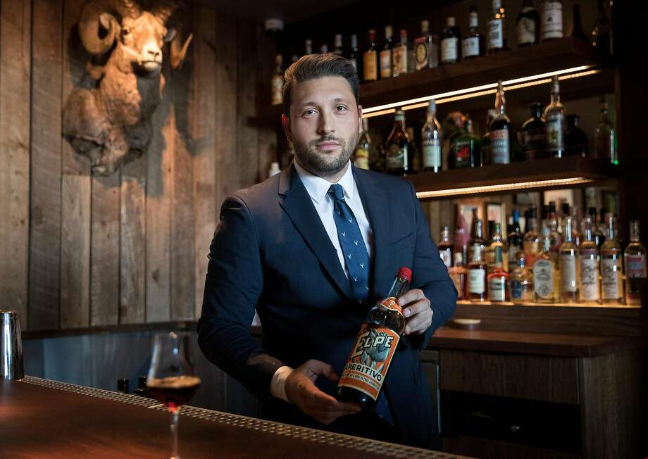 Bar Director Brandyn Tepper holds a bottle of Elpe Carciofio from the 1960s, one of the many vintage spirits he carries at Angler. Photo: Jessica Christian / The Chronicle