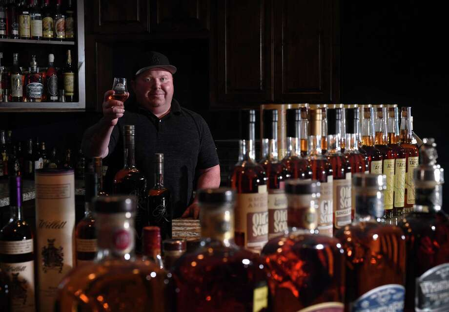 Founder of the Southeast Texas Bourbon Scene, Jonathan Richard's holds up a Glencairn glass while surrounded by his extensive collection of bourbons at home.  Photo taken Wednesday, 10/24/18 Photo: Guiseppe Barranco/The Enterprise, Photo Editor / Guiseppe Barranco ©