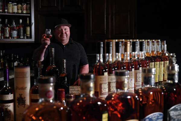 Founder of the Southeast Texas Bourbon Scene, Jonathan Richard's holds up a Glencairn glass while surrounded by his extensive collection of bourbons at home. Photo taken Wednesday, 10/24/18