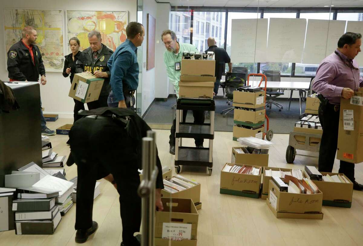 Police Investigator with the Harris County District Attorney's Office are shown loading files after serving a search warrant at the Woodfill Law Firm, 3 Riverway #750, Monday, Nov. 12, 2018, in Houston. The founding partner is Jared Woodfill.