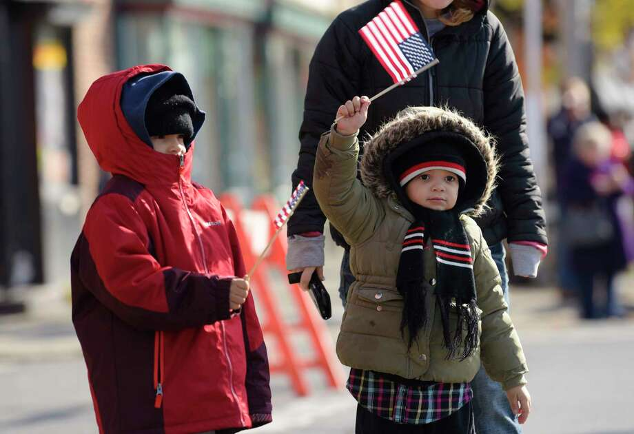 Lawrence Wilburn, 8, of Albany and his sister, Annabell Wilburn, 5, wave flags as they watch the Veterans Day Parade on Monday, Nov. 12, 2018, in Albany, N.Y.  (Paul Buckowski/Times Union) Photo: Paul Buckowski, Albany Times Union / (Paul Buckowski/Times Union)