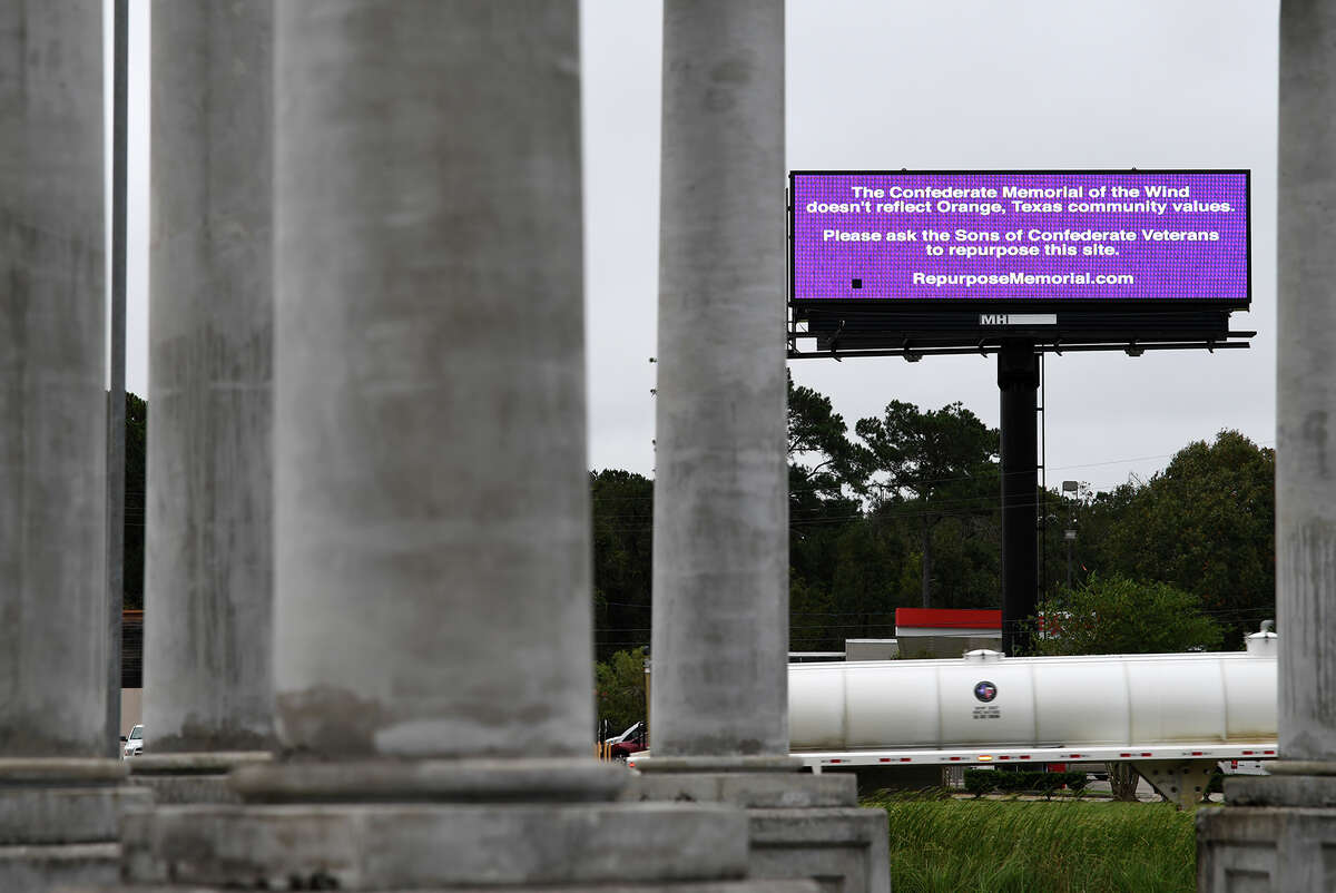 A billboard seen through the Confederate monument in Orange requests that the monument be repurposed. Photo taken Monday, 11/12/18