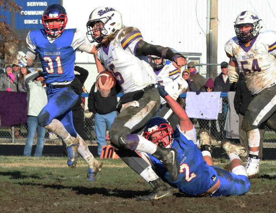 Williamsville quarterback Damon Coady tries to get free from the grasp of Carlinville cornerback Colton DeLong (2) while the Cavs' Kyle Dixon (31) and the Bullets' Brad Olysav (54) pursue the play Saturday in a Class 3A quarterfinal game at Carlinville. Photo: Greg Shashack / The Telegraph