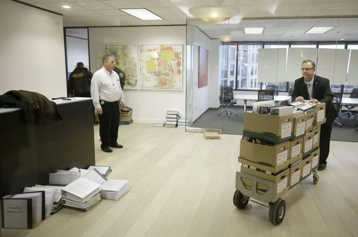 Investigators with the Harris County District Attorney's Office remove files after serving a search warrant at the Woodfill Law Firm, 3 Riverway #750, Monday, Nov. 12, 2018, in Houston. The founding partner is Jared Woodfill.