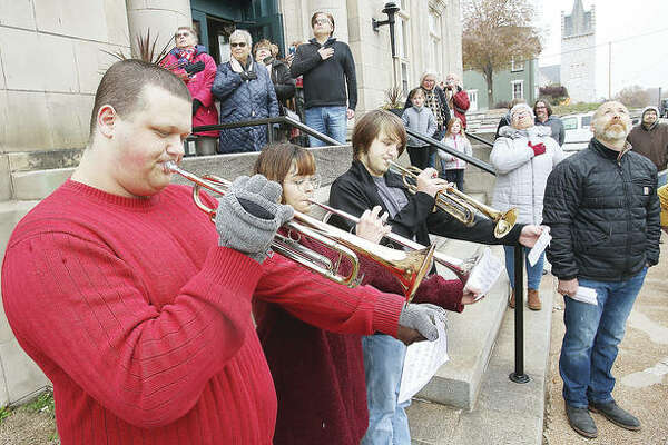 Trumpet players from the Alton High School Marching 100 play Monday at a ceremony to raise the American flag above the Post Commons for the first time in more than 50 years.