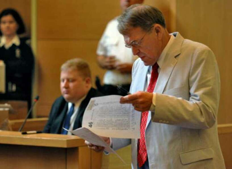 Defense attorney Terence Kindlon examines a photocopy of a toll ticket from the New York State Thruw