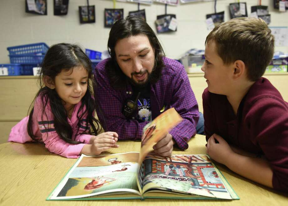 Counselor Steven Moore reads to first-graders Ximena Vargas and Emmett Marranca at the Byram Archibald Neighborhood Center in the Byram setion of Greenwich, Conn. Thursday, Nov. 1, 2018. The center provides valuable and thrifty after school care for children in Western Greenwich. Photo: Tyler Sizemore / Hearst Connecticut Media / Greenwich Time