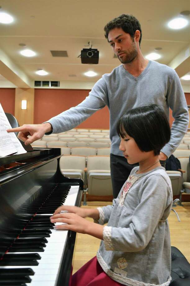 Zachary Saffa instructs Kayla Huang, 9, of Greenwich, at the Studio Showcase Series at Darien Library, Sunday evening, Nov. 11, 2018, in Darien, Conn. Photo: Jarret Liotta / For Hearst Connecticut Media / Darien News Freelance
