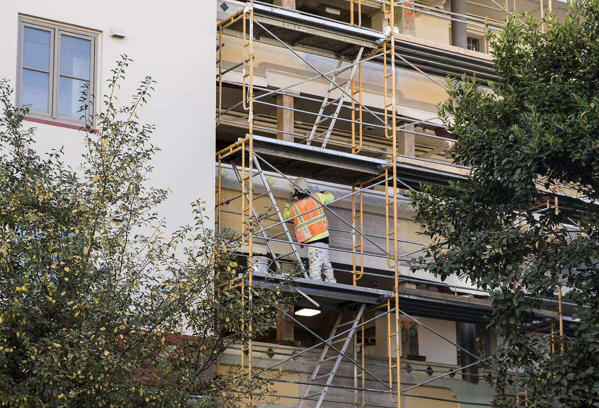 A construction worker paints the exterior of the Ping Yuen Center housing project in the Chinatown neighborhood of San Francisco, Calif. Thursday, Nov. 8, 2018.
