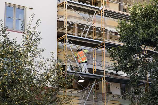 3of4a Construction Worker Paints The Exterior Of Ping Yuen Housing Project In San Francisco S Chinatown Photo Jessica Chronicle