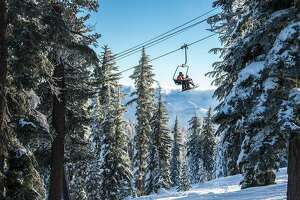 Skiers and snowboarders climb the mountain by lifts at Northstar California Resort.