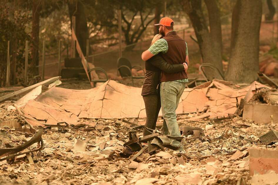 Chris and Nancy Brown embrace while looking over the remains of their burned residence after the Camp fire tore through the region in Paradise, California on November 12, 2018. - Thousands of firefighters spent a fifth day digging battle lines to contain California's worst ever wildfire as the wind-whipped flames cleaved a merciless path through the state's northern hills, leaving death and devastation in their wake. The Camp Fire -- in the foothills of the Sierra Nevada mountains north of Sacramento -- has killed 29 people, matching the state's deadliest ever brush blaze 85 years ago. More than 200 people are still unaccounted for, according to officials. (Photo by Josh Edelson / AFP)JOSH EDELSON/AFP/Getty Images