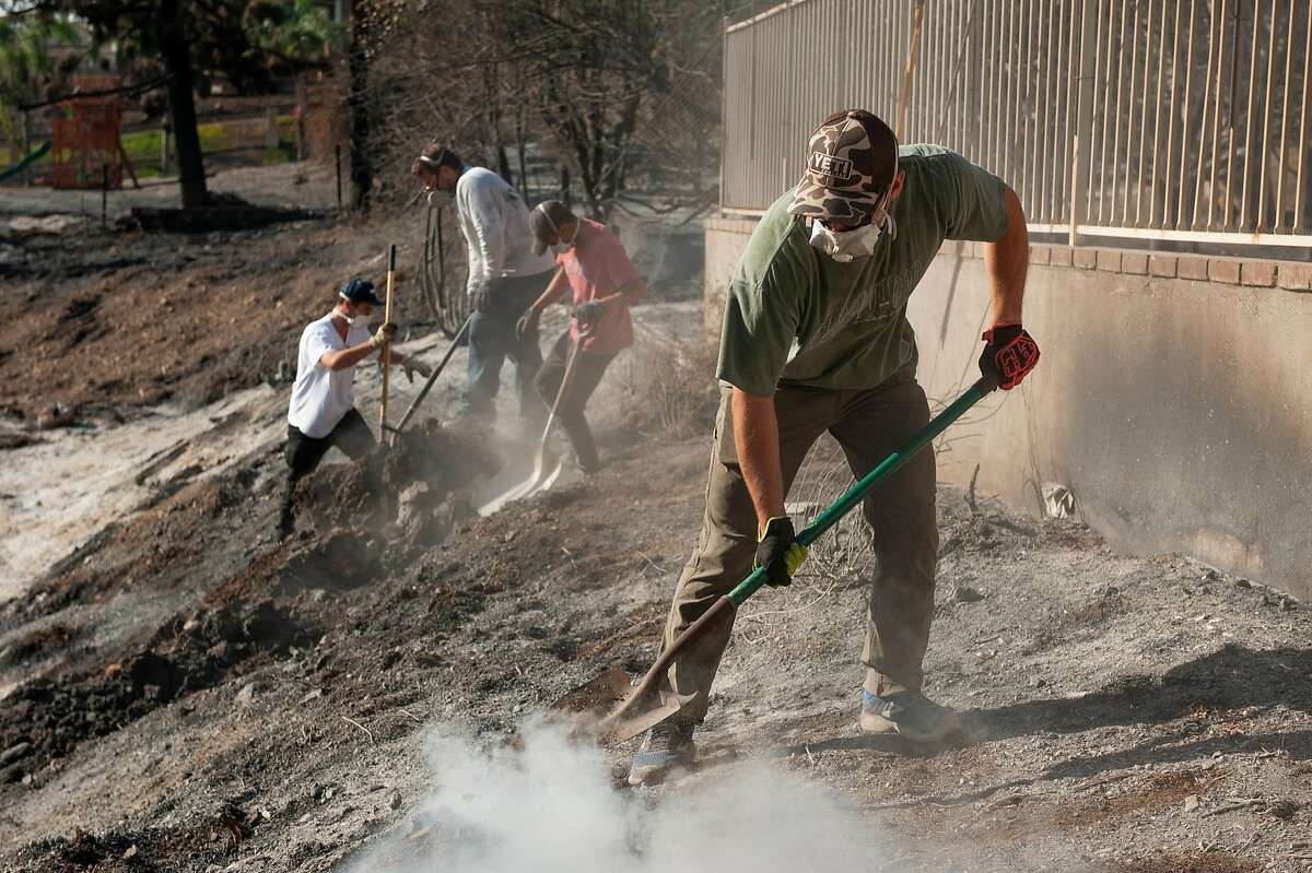 Griffin Dyne works to extinguish hotspots in a neighborhood damaged by the Woolsey Fire in Malibu, Calif., Nov. 11, 2018. Firefighters battling the Woolsey Fire in Southern California were preparing for it to get worse over the next few days. Two people have died in that fire, which is 20 percent contained and has charred more than 90,000 acres in communities like Malibu and Thousand Oaks. (Andrew Cullen/The New York Times)
