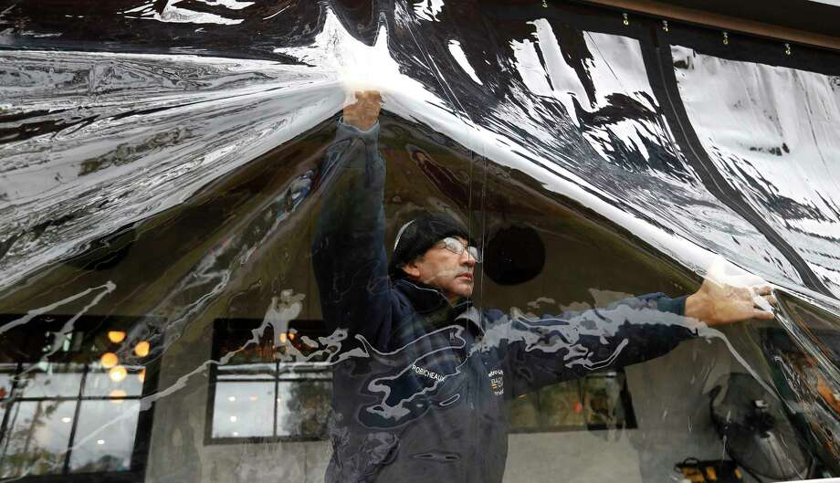 Hector Castro with Gulf Coast Canvas Awnings pushes back from gusts of wind as Juan Guzman and Boris Torres install a clear plastic patio enclosure for the restaurant Calle Onze at 222 W. 11th in the Heights, as winter weather decended, Monday, Nov. 12, 2018, in Houston. Photo: Karen Warren, Staff Photographer / © 2018 Houston Chronicle