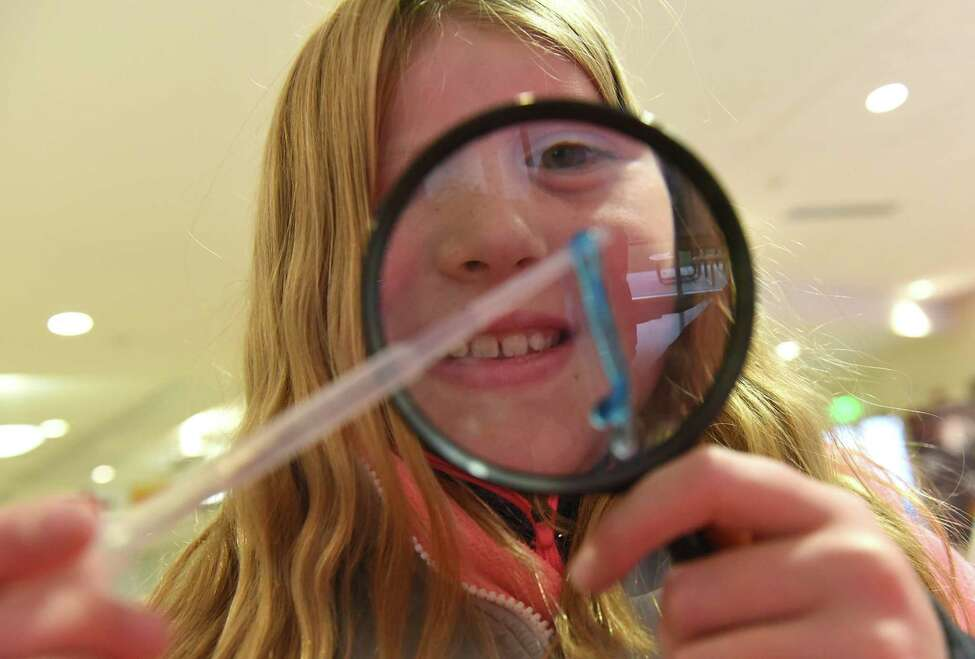 Gordon Creek Elementary School student Mckenna Halbohm, 8, of Ballston Spa looks uses a semi-conductor to look for DNA on a plastic worm in a forensic science experiment during an educational outreach initiative and Veterans Day celebration in the GLOBALFOUNDRIES Fab 8 GlobalCafe on Monday, Nov. 12, 2018 in Malta, N.Y. The event featured both a STEM expo as well as interactive workshops including STEM activities. (Lori Van Buren/Times Union)
