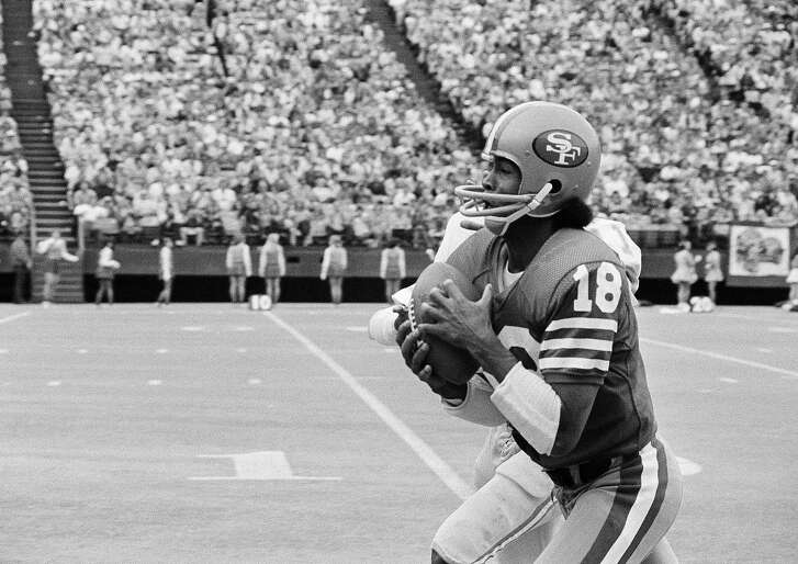 San Francisco 49ers wide receiver Gene Washington (18) tucks in a Jim Plunkett pass in third quarter to score on a 48-yard play in San Francisco, Oct. 24, 1977. The 49ers took their first victory of the season with a 28-7 win over the Detroit Lions.  (AP Photo/Sal Veder)