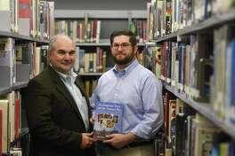 "Stamford resident Tony Pavia and his son, Matt Pavia, a teacher at Darien High School, show their new book ""An American Town and the Vietnam War"" during a reception at Darien High School in Darien on Monday. The book documents stories of Stamford veterans and their service in the Vietnam War."