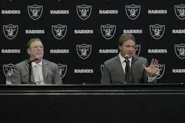 Jon Gruden (right), Oakland Raiders head coach, sits between Oakland Raiders owner Mark Davis (left) speak to the media after Gruden was introduced as the new head coach of the Oakland Raiders at Raiders Headquarters on Tuesday, January 9, 2018 in Alameda, Calif.