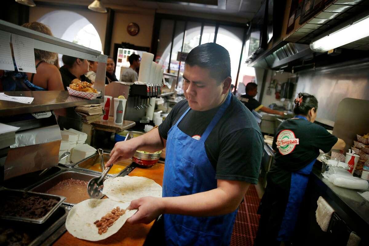 Salomon Gonzalez makes a carnitas super burrito at La Taqueria on Wednesday, September 10, 2014 in San Francisco, Calif.