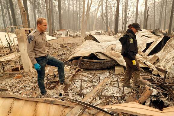 Chico Police Chaplin Dan Wysong and Butte County Investigator Tiffany Larson search for victims of the Camp Fire in the Pine Springs Mobile Home Park in Paradise, Calif. on Monday, November 12, 2018. Both Wysong and Larson lost their Paradise homes in the wildfire.