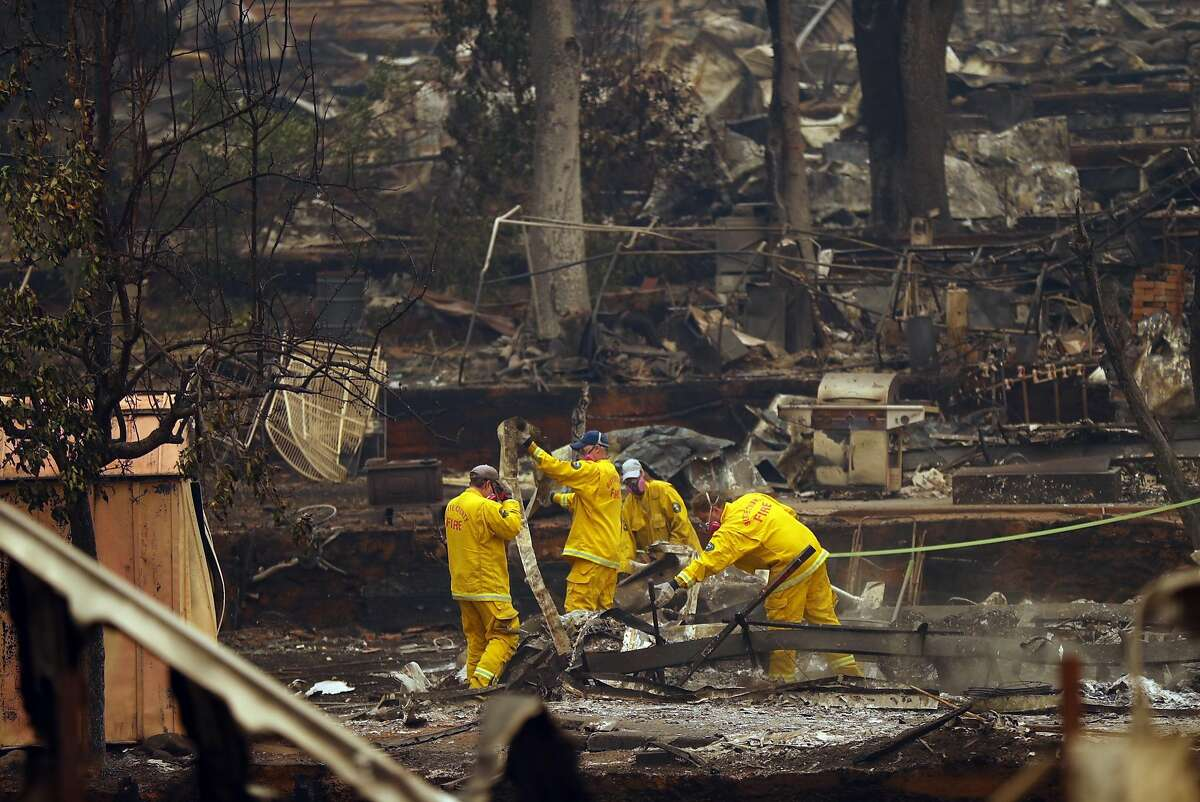 Butte County Fire Department members search the Skyway Villa Mobile Home Park for fire victims in aftermath of Camp Fire in Paradise, Calif. on Monday, November 12, 2018.