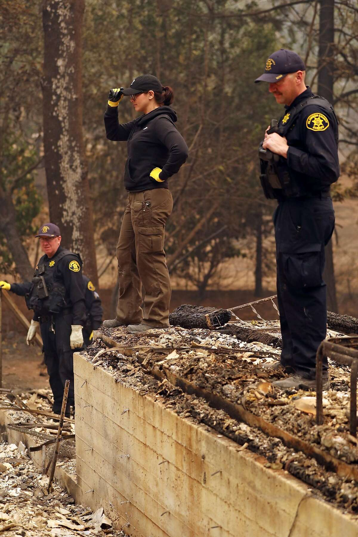 Butte County Investigator Tiffany Larson is flanked by Alameda County Sheriff's Deputies Jeff Hovda (left) and Jason Henshaw (right) as they search for victims in aftermath of Camp Fire in Paradise, Calif. on Monday, November 12, 2018.