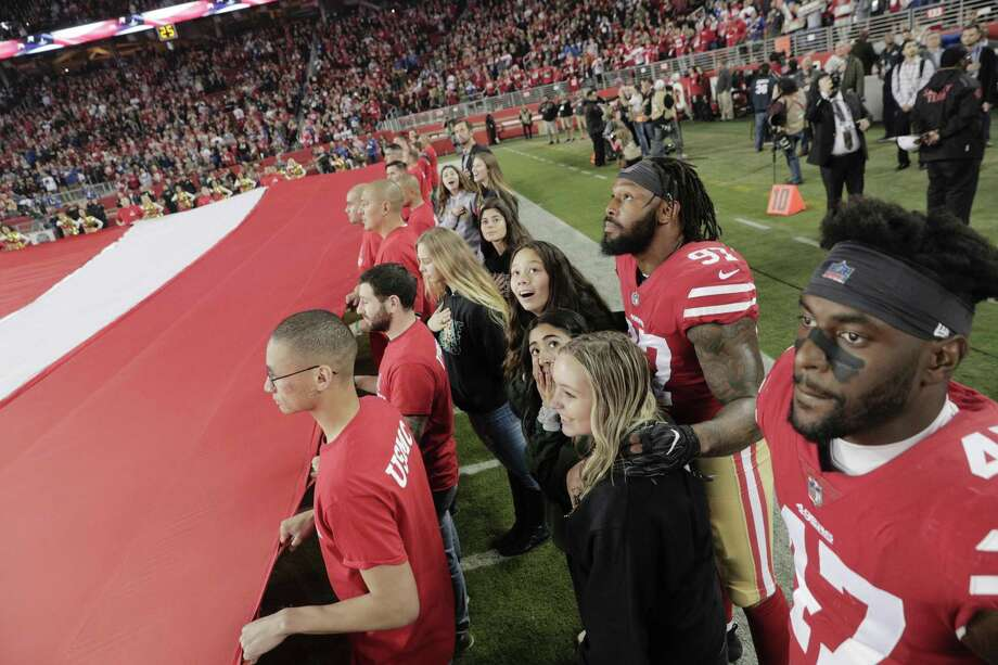 Players from the San Francisco 49ers listen to the National Anthem alongside football players and cheerleaders from Paradise High School at Levi's Stadium before the San Francisco 49ers played the New York Giants at Levi's Stadium in Santa Clara, Calif., on Monday, November 12, 2018. Photo: Carlos Avila Gonzalez / The Chronicle