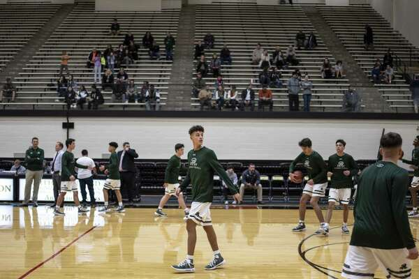 "Senior Kaeyel Moore, no. 22, center, warms up with his teammates as he returns to the basketball court for the Reagan High School Rattlers on Monday, November 12, 2018. Moore suffered a cardiac arrest on the practice gym 10 months ago. Head coach John Hirst said that it's good to have him back. ""It's a miracle if you think about it,"" he said. Moore played briefly in his team's first game of the season."