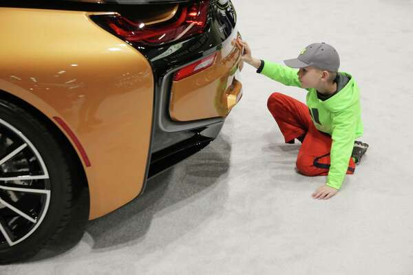Visitors check out a 2019 BMW i8 Roadster during the 2018 Seattle International Auto Show at the CenturyLink Field Event Center, Monday, Nov. 12, 2018. The show, which ran from Nov. 9-12, included over 500 2019 model cars from foreign and domestic companies, as well as older classic exhibition cars.