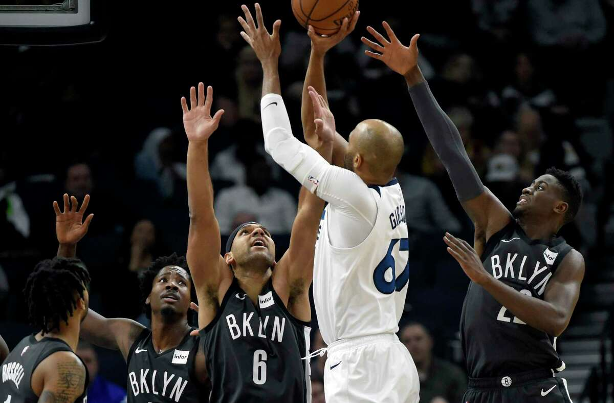 Brooklyn Nets' Ed Davis, left, Jared Dudley (6) and Caris LeVert (22) defend against a shot by Minnesota Timberwolves' Taj Gibson (67) during the second quarter of an NBA basketball game on Monday, Nov. 12, 2018, in Minneapolis. (AP Photo/Hannah Foslien)