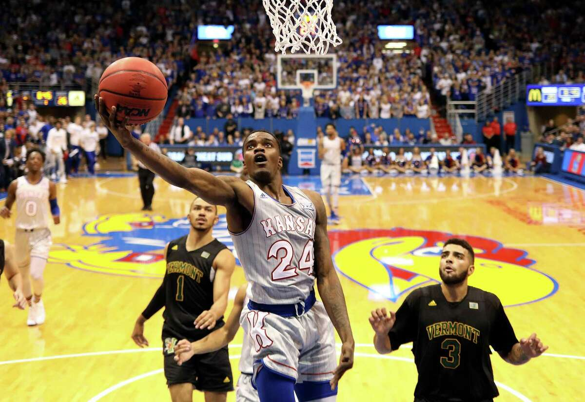 LAWRENCE, KANSAS - NOVEMBER 12: Lagerald Vick #24 of the Kansas Jayhawks scores on a fast break as Skyler Nash #1 and Anthony Lamb #3 of the Vermont Catamounts defend during the game at Allen Fieldhouse on November 12, 2018 in Lawrence, Kansas. (Photo by Jamie Squire/Getty Images)