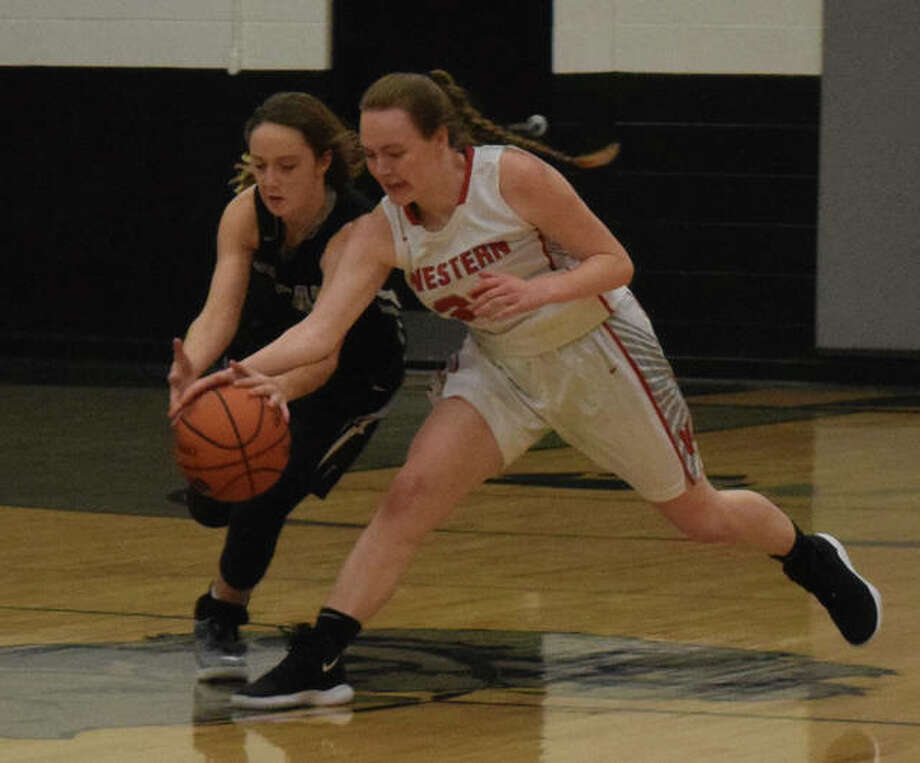 West Central's Madi DeJaynes (left) fights for control of the ball Monday night. Photo: Audrey Clayton | Journal-Courier