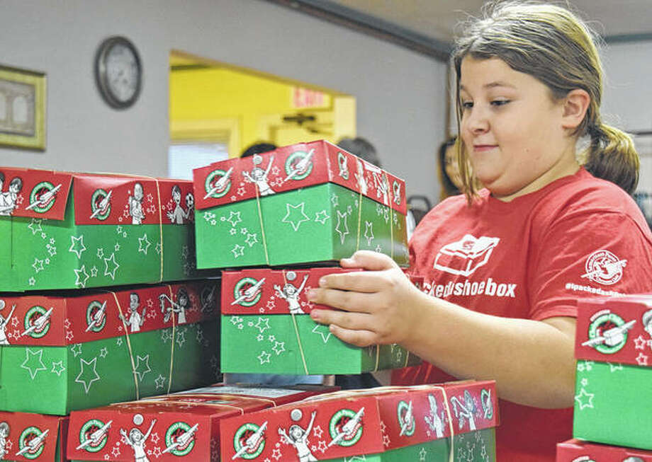 Emma Ford, 9, daughter of Steve and Sarah Ford of Chapin, collects boxes for Operation Christmas Child on Monday at Calvary Baptist Church. The program delivers toys, school and hygiene supplies for needy children around the world. Boxes are available at the church or regular shoeboxes can be filled with supplies and dropped off 4-7 p.m. Tuesday through Thursday, 10 a.m.-2 p.m. Friday through Saturday, 1-4 p.m. Sunday and 9-11 a.m. Monday.